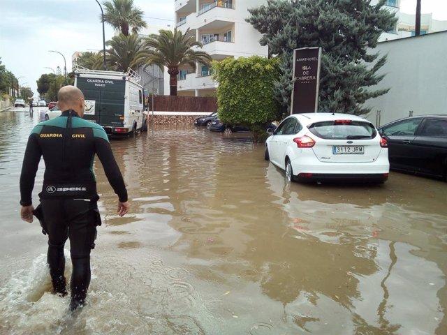 Archivo - Un agente camina en una carretera afectada por una inundación en el sur de Mallorca.
