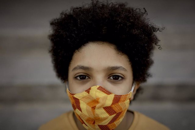 Archivo - El niño actor y modelo Hugo Ndiaye, de 10 años, cruza un paso de cebra con una pelota de baloncesto. En Madrid (España) a 28 de mayo de 2020.