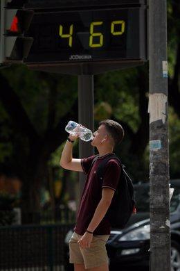 Un hombre bebe agua junto a un termómetro que marca 46º durante un día de alerta roja por altas temperaturas, a 12 de julio de 2021, en la ciudad de Murcia, Murcia (España)