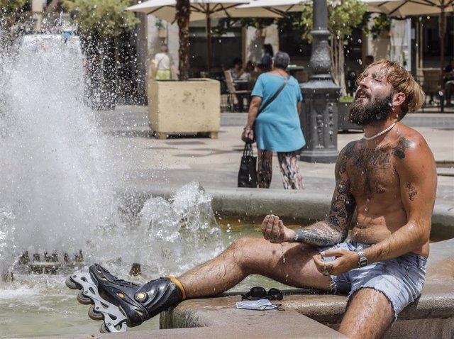 Un hombre se refresca en una fuente (archivo)