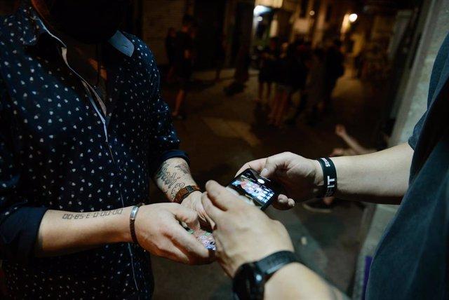 Un hombre muestra en su móvil un certificado de prueba PCR a las puertas de un local de ocio nocturno, en el centro de Ourense, a 10 de julio de 2021, en Ourense, Galicia (España).