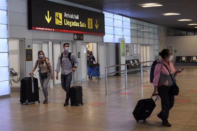 Pasajeros procedentes de un vuelo con origen Gran Bretaña llegan a la terminal T1 del Aeropuerto Adolfo Suárez Madrid-Barajas en Madrid (España).
