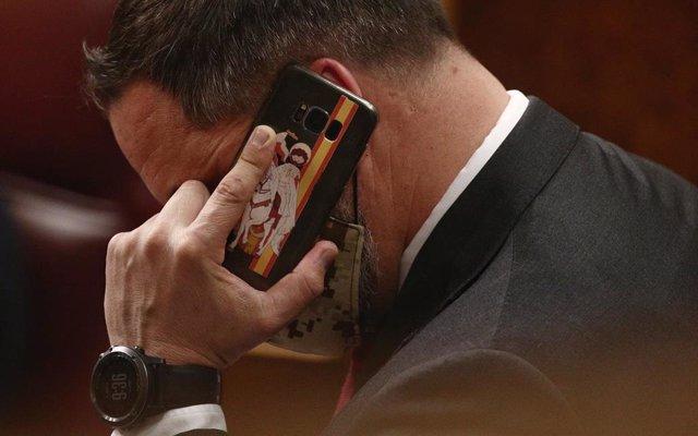 Archivo - El líder de Vox, Santiago Abascal, habla por teléfono durante una sesión plenaria