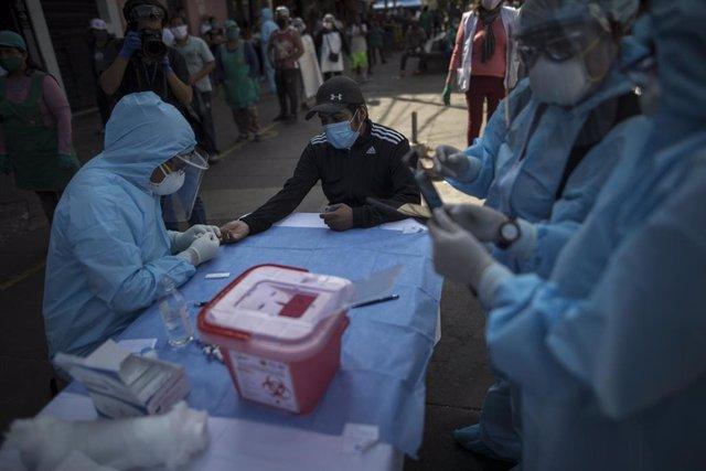 Archivo - Un trabajador sanitario toma muestras en Lima, Perú.