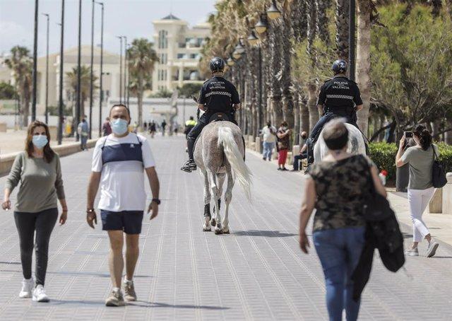 Archivo - Arxiu - Dos policies municipals patrullen a cavall per un passeig marítim enfront d'una platja de València, a 26 de maig de 2021