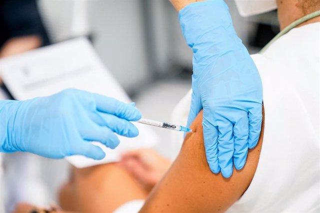 Un enfermero vacuna a un paciente.