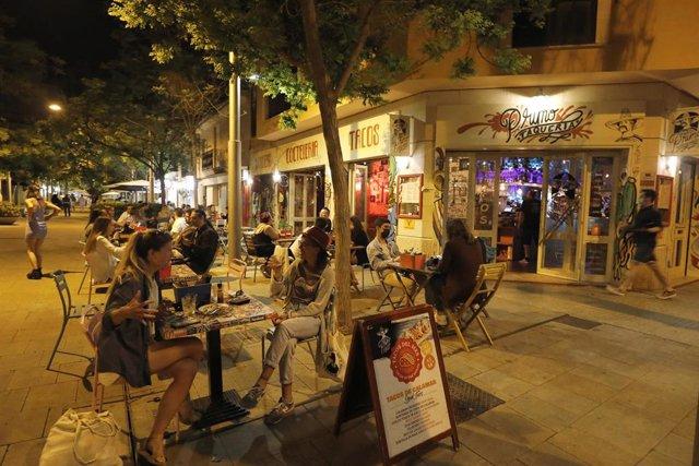 Archivo - Gente en un bar de Palma por la noche.