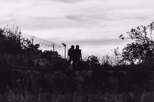Archivo - Dos agentes frente a la frontera que separa Melilla y Marruecos en una imagen de archivo.