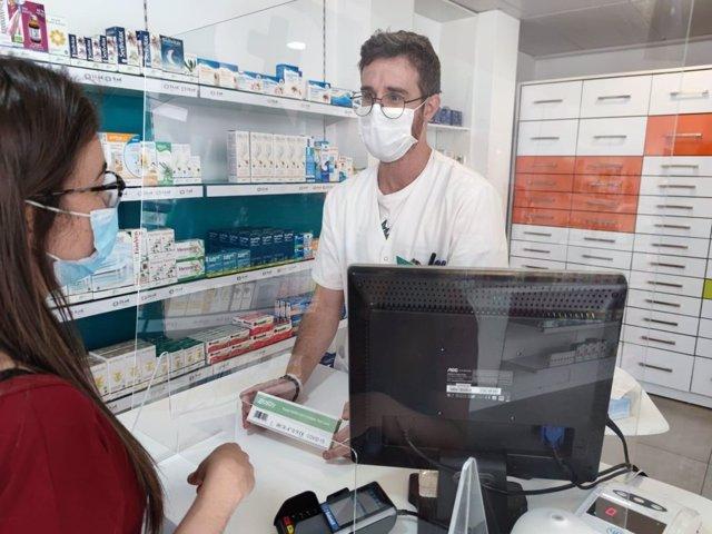 Un farmacéutico dispensa un test de autodiagnóstico