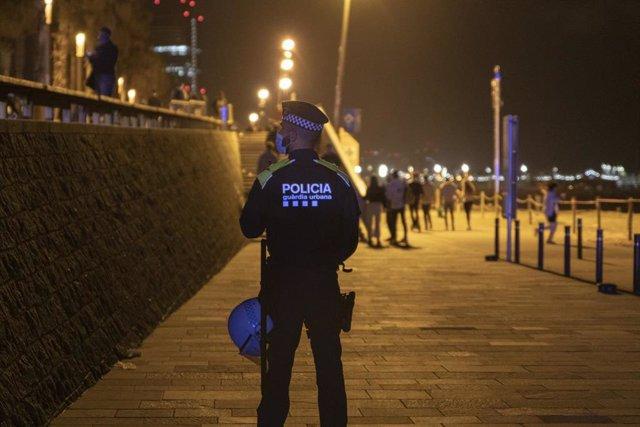 Archivo - Un agente de Policía vigila la playa de la Barceloneta durante el primer viernes sin toque de queda, a 14 de mayo de 2021, en Barcelona, Catalunya, (España). Este es el primer viernes sin toque de queda donde se han vuelto a repetir las imágenes