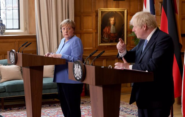 02 July 2021, United Kingdom, Buckinghamshire: UK Prime Minister Boris Johnson (R) and German Chancellor Angela Merkel, hold a joint press conference after their meeting at Chequers, the country house of the Prime Minister of the United Kingdom, in Buckin