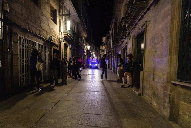 Un coche de policía pasa frente a varias personas en ambiente festivo, a 10 de julio de 2021, en Pontevedra, Galicia (España).