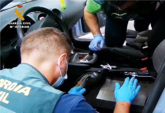 Agentes inspeccionan el doble fondo del vehículo donde ocultaban la droga
