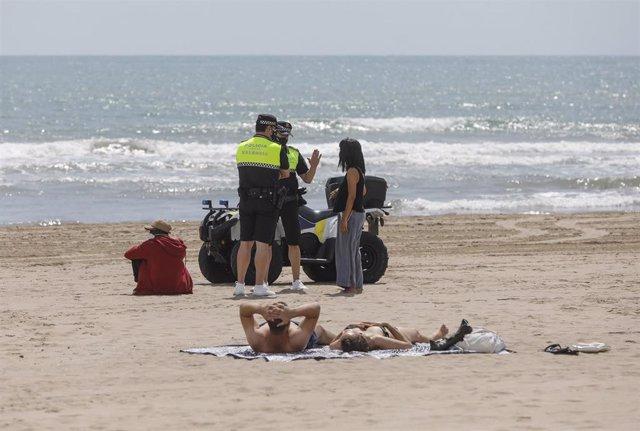 Archivo - Dos policías municipales hablan con una mujer en una playa de València (archivo)