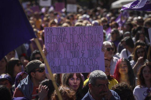 Archivo - Una mujer sostiene su pancarta con un mensaje de protesta en contra de la prostitución durante la manifestación por el Día Internacional de la Mujer en Sevilla, (Andalucía, España), a 08 de marzo de 2020