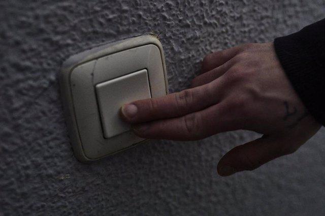 Archivo - Un hombre toca una llave de la luz (archivo)