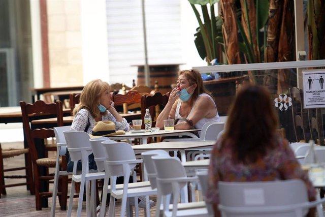 Archivo - Una persona fuma en una terraza. En Málaga, (Andalucía, España), a 17 de agosto de 2020.