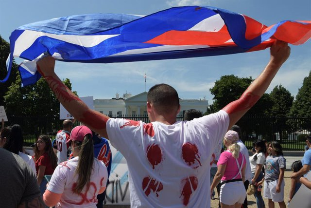 13 July 2021, US, Washington: Cuban demonstrators from We are more and We are not afraid's movement holds a Cuban flag during a rally in front of the White House to show their support for the people in Cuba that have taken to the streets to protest pandem