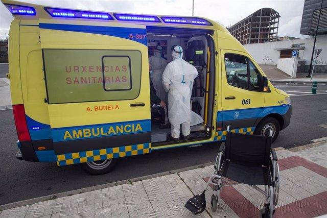 Archivo - Un trabajador sanitario totalmente protegido ayuda a subir a la ambulancia a un anciano de una residencia en Galicia.