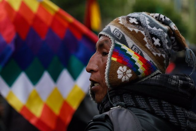 """Archivo - 12 November 2019, Bolivia, La Paz: A Supporter of Bolivian former President Evo Morales, shout slogans and holds the """"wiphala"""" flag that represent the nation's indigenous people, takes part in a protest. Photo: Gaston Brito/dpa"""