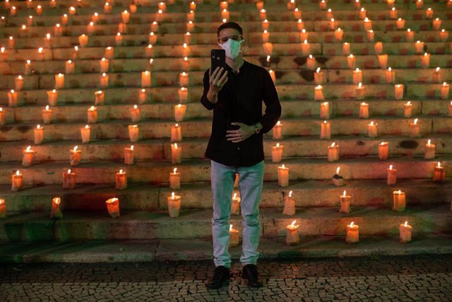 Archivo - 21 June 2021, Brazil, Rio De Janeiro: A man takes a selfie with the 500 candles that people lit in memory of the 500,000 people who have died so far in Brazil from the coronavirus (Covid-19). Photo: Fernando Souza/dpa