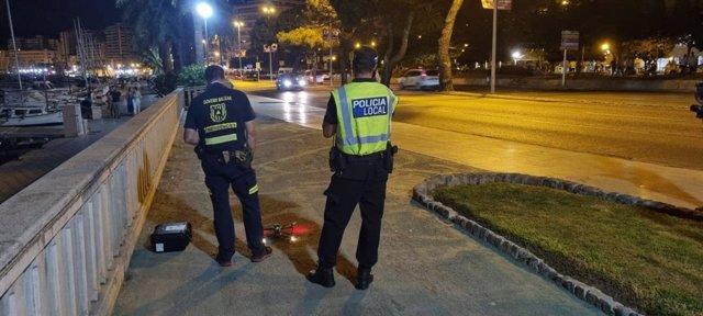 Un agente de la Policía Local y un agente de la dirección General de Emergencias del Govern junto al dron utilizado en el dispositivo antibotellón.