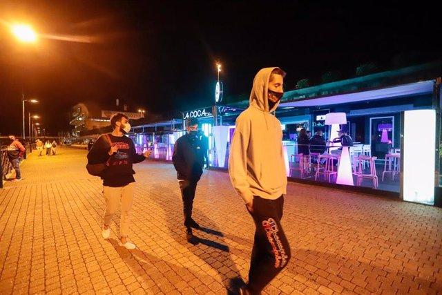 Mozos pasean por unha zona de locais de lecer nocturno, a 23 de xullo de 2021, en Sanxenxo, Pontevedra, Galicia (España). Este sábado entran en vigor novas medidas que afectan o sector da hostalaría e o lecer nocturno en Galicia. Así, nos ayuntam