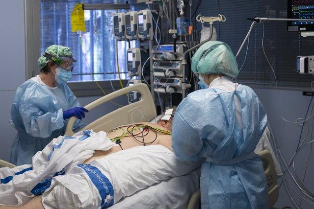 Archivo - Arxiu - Personal sanitari atenent a un pacient ingressat en l'Unitat de Vigilància intensiva (UCI).