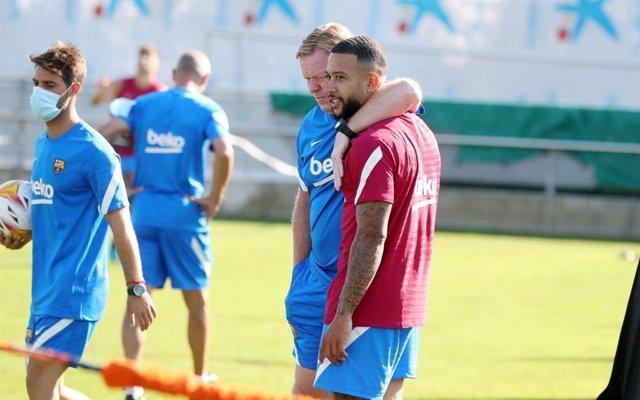 El entrenador del FC Barcelona, Ronald Koeman, abraza a su nuevo jugador Memphis Depay en su primer entrenamiento con el equipo blaugrana, el 20 de julio de 2021