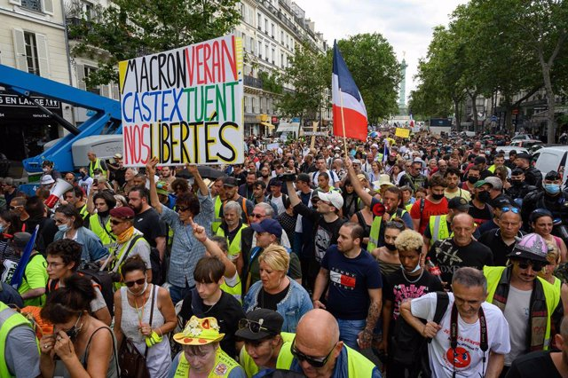 24 July 2021, France, Paris: People holds placards and flags during a demonstration at the Place de la Bastille with the Yellow Vests against the health pass imposed by the government. Photo: Julien Mattia/Le Pictorium Agency via ZUMA/dpa