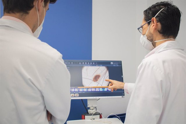 Archivo - Profesionales sanitarios observan la imagen de una melanoma cutáneo