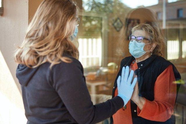 Archivo - Nieta visitando a la abuela durante la pandemia