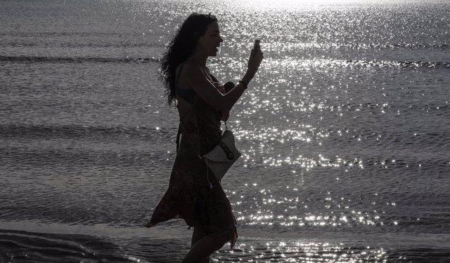 Archivo - Una mujer mira el móvil en la playa de la Malvarrosa