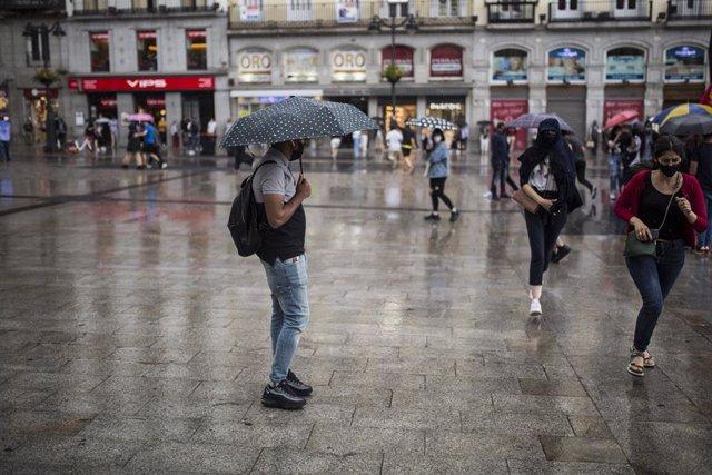 Archivo - Arxiu - Ciudadanos protegint-se de la pluja durant una manifestació en la Porta del Sol el passat 5 de juny a Madrid