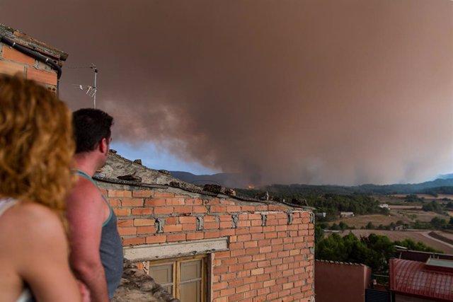 Veïns amb fum de l'incendi al fons, a 25 de juliol de 2021, a Sant Martí de Tous, Barcelona, Catalunya (Espanya).