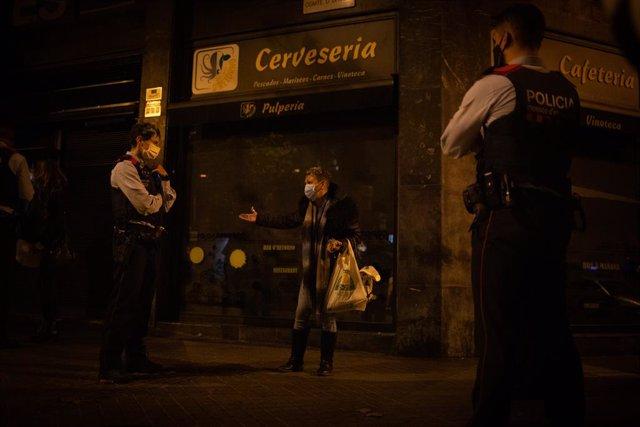 Archivo - Arxiu - Diversos mossos paren una persona en un control durant el toc de queda
