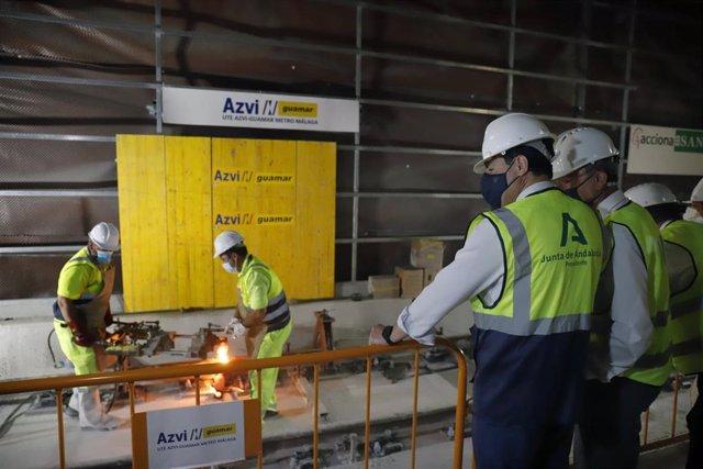 El presidente de la Junta de Andalucía, Juanma Moreno (c), asiste a la primera soldadura del carril de vía en la estación de Atarazanas del metro. A 26 de julio de 2021, en Málaga (Andalucía, España).