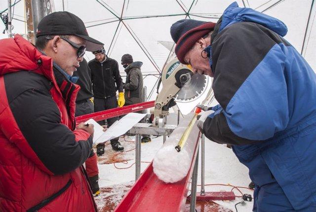 Yao Tandong, izquierda, y Lonnie Thompson, derecha, procesan un núcleo de hielo extraído del casquete glaciar Guliya en la meseta tibetana en 2015. El hielo contenía virus de casi 15.000 años de antigüedad, según un nuevo estudio.