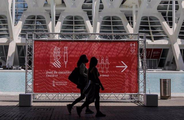 Archivo - Dos personas pasan por un cartel que indica el punto de vacunación de la Ciudad de las Artes y las Ciencias de València.