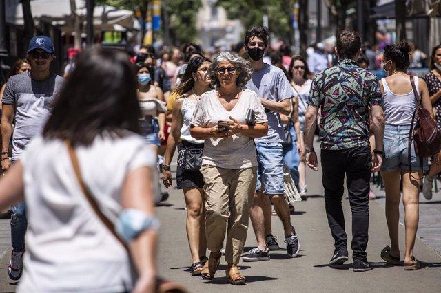 Archivo - Una mujer pasea sin mascarilla por el centro de Madrid, durante el primer día en el que no es obligado el uso de la mascarilla en exteriores desde el inicio de la pandemia, a 26 de junio de 2021, en Madrid (España). El 30 de marzo de 2020 el Bol