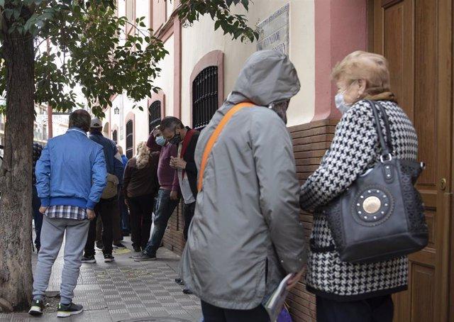Archivo - Colas en la puerta del comedor social Ntra. Sñra. del Rosario de las Hijas de la Caridad de San Vicente de Paúl en Triana, que ha incrementado sus usuarios y usuarias en el actual contexto de pandemia por la COVID-19 y sus consecuencias económic
