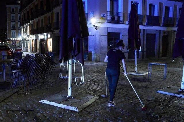 Archivo - Una trabajadora recoge la terraza de una cafetería de Madrid.