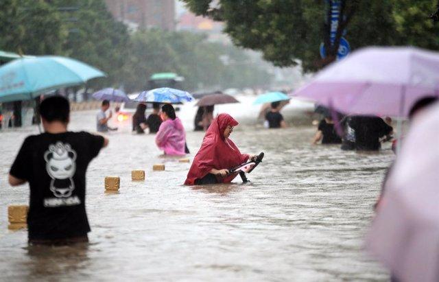 Gente camina por la carretera inundada después de lluvias récord en la ciudad de Zhengzhou, en la provincia central china de Henan.