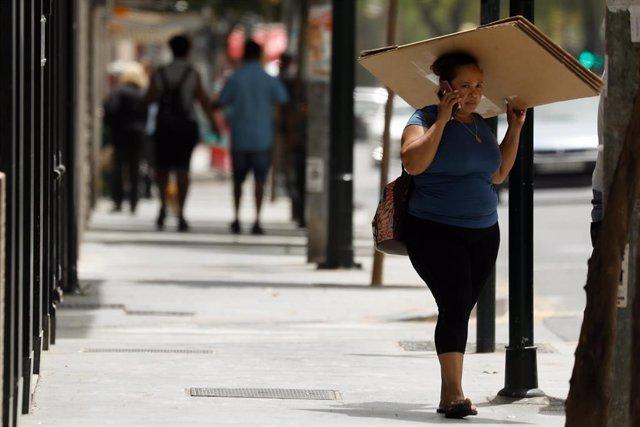 Una mujer se protege del sol con una caja de cartón en una foto de archivo.