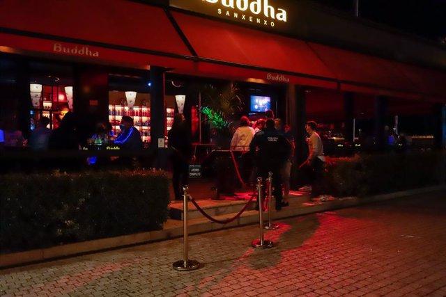 Diverses persones esperen les portes d'un local d'oci nocturn en Sanxenxo, Pontevedra, Galícia (Espanya).