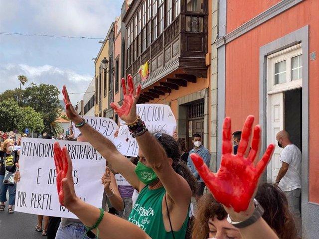 Varias personas con las manos pintadas de roja se manifiestan por los derechos de los migrantes.