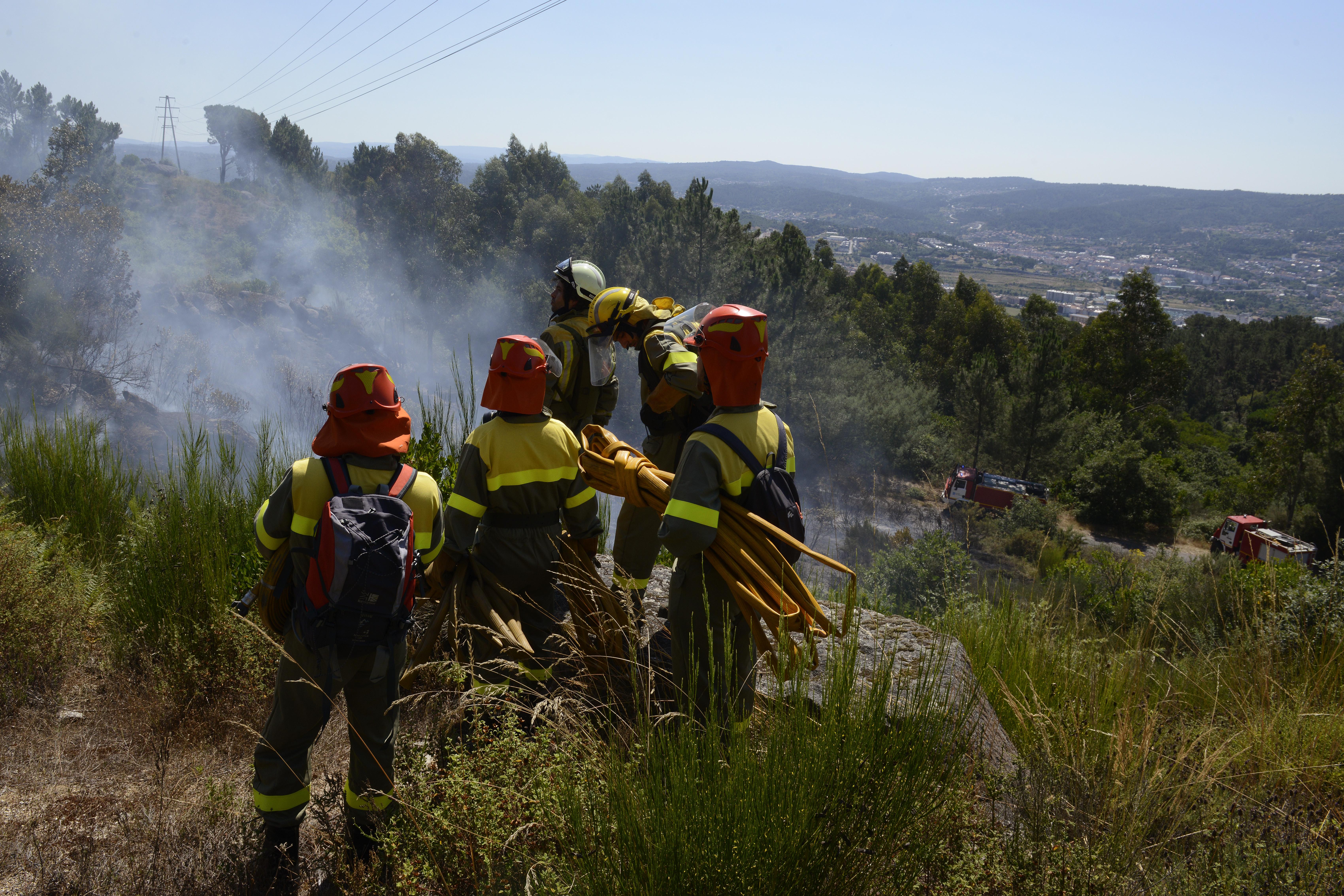 Un grupo de bomberos, durante las labores para controlar un incendio forestal, a 28 de julio de 2021, en la parroquia de Santa Mariña do Monte, Ourense, Galicia (España)