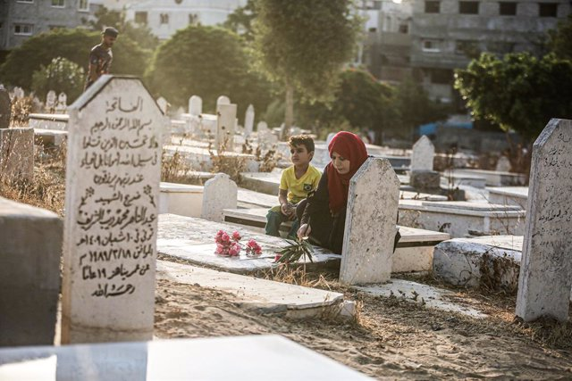20 July 2021, Palestinian Territories, Gaza City: A Palestinian family visits the graves of their relatives during the Eid al-Adha at a cemetery in Gaza city. Eid al-Adha is the holiest feast in Islam, during which Muslims slaughter cattle and sheep to co