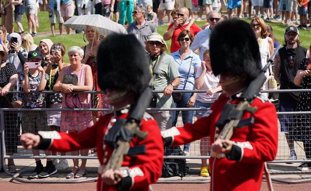22 July 2021, United Kingdom, Windsor: People watch as members of the 1st Battalion Grenadier Guards take part in the Changing of the Guard at Windsor Castle in Berkshire, which is taking place for the first time since the start of the coronavirus pandemi