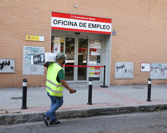 Archivo - Un repartidor pasa por una oficina del SEPE